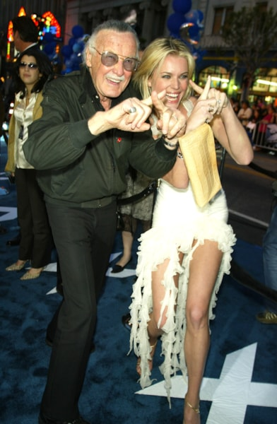 """LOS ANGELES - APRIL 28:  X-Men creator Stan Lee (L) and actress Rebecca Romijn-Stamos pose at the premiere of """"X2: X-MEN UNITED"""" at the Chinese Theatre on April 28, 2003 in Los Angeles, California. (Photo by Kevin Winter/Getty Images)"""