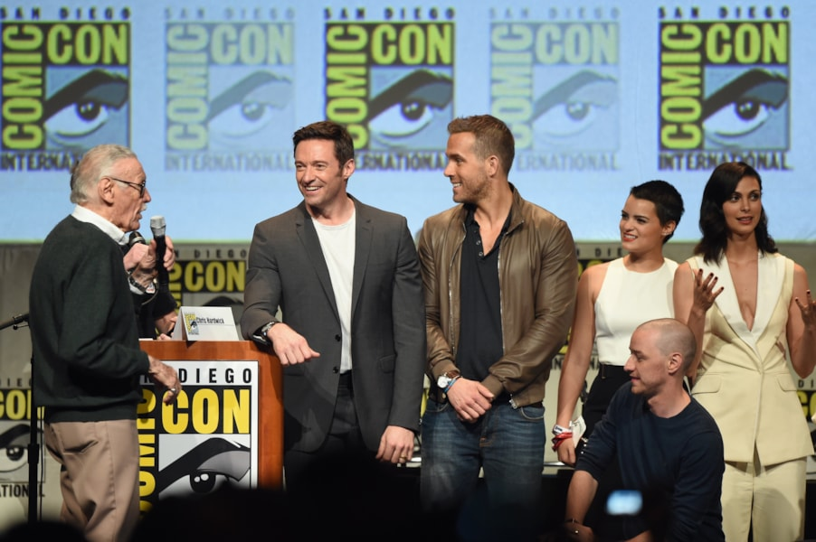 SAN DIEGO, CA - JULY 11:  (L-R) Stan Lee, actor Hugh Jackman, actor Ryan Reynolds, actress Brianna Hildebrand, actor James McAvoy (kneeling) and actress Morena Baccarin appear onstage at the 20th Century FOX panel during Comic-Con International 2015 at the San Diego Convention Center on July 11, 2015 in San Diego, California.  (Photo by Kevin Winter/Getty Images)