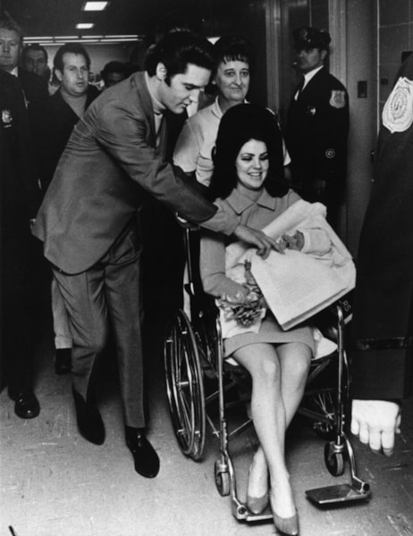 Singer Elvis Presley (1935 - 1977), 33, and his 22 year-old wife Priscilla, leaving the Baptist Hospital, Memphis, Tennessee, with their baby daughter Lisa-Marie, born at the hospital on February 2nd.    (Photo by Keystone/Getty Images)
