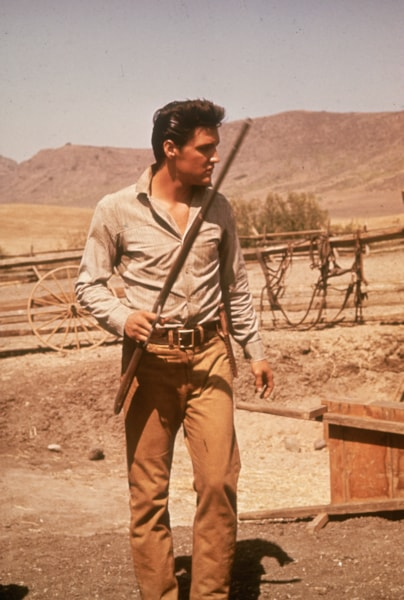American film star Elvis Presley (1935 - 1977) strides around a ranch with a gun in his hand.   (Photo by Hulton Archive/Getty Images)